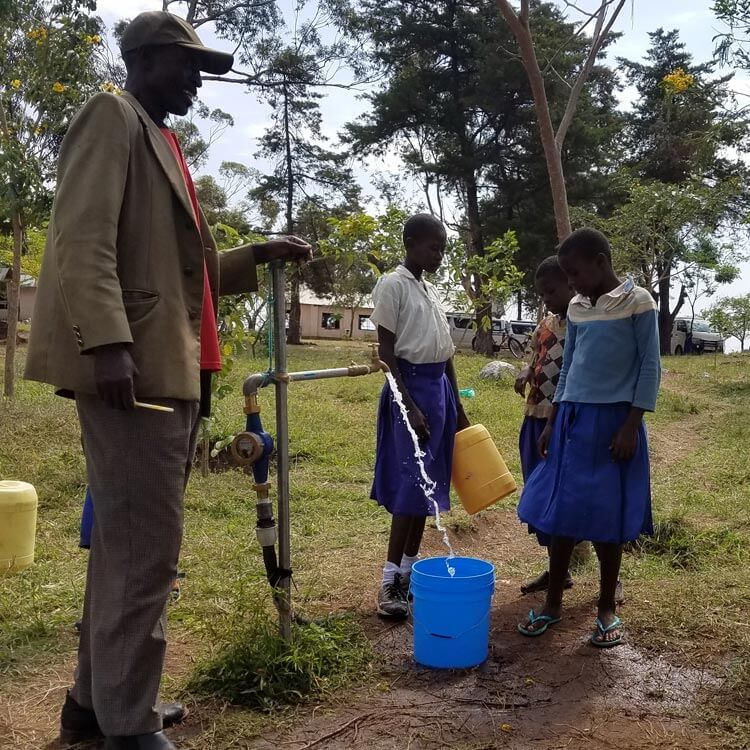 Photo of children filling up a bucket with water