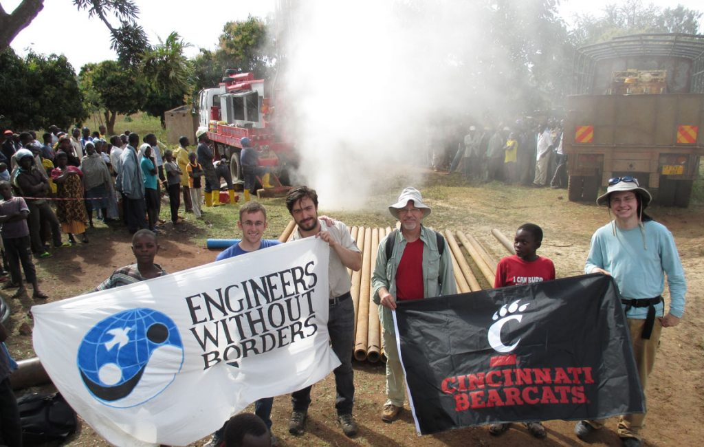 """Photo of individuals holding flags: """"Engineers without Borders"""" and """"Cincinnati Bearcats"""""""