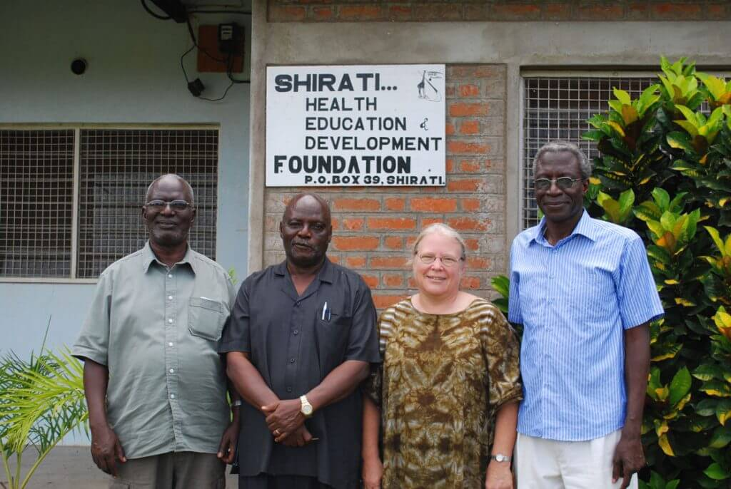 Photo of individuals standing outside of the Shirati Health Education Foundation (SHED)