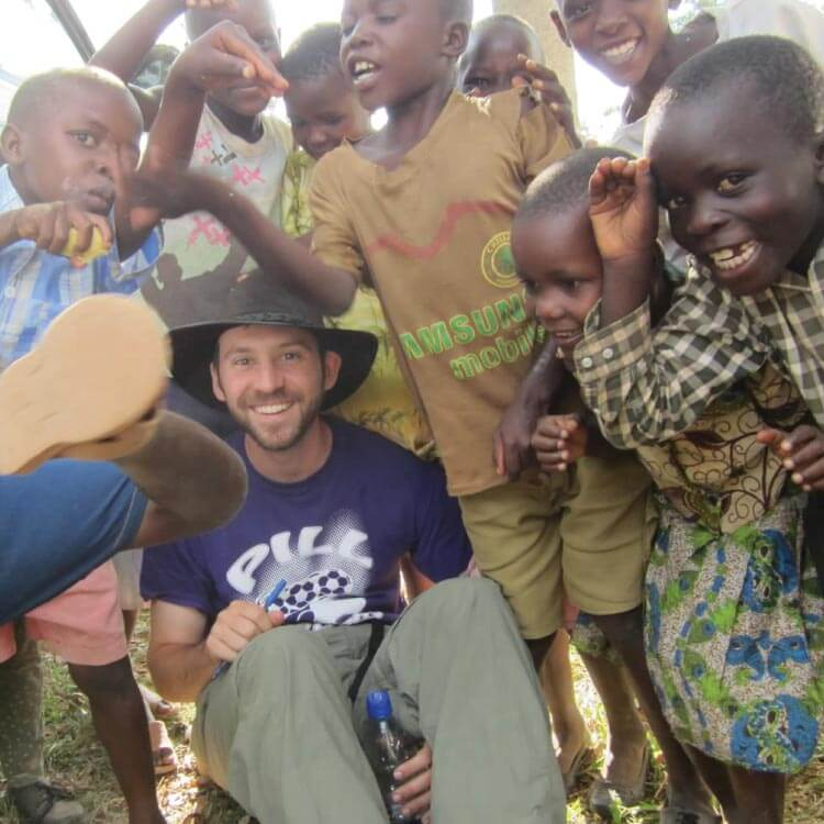 Photo of a man volunteering with several children