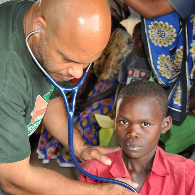 Photo of Chris Lewis examining a child with a stethoscope