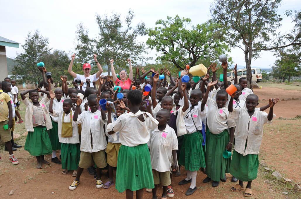 Group of school children and volunteers cheering