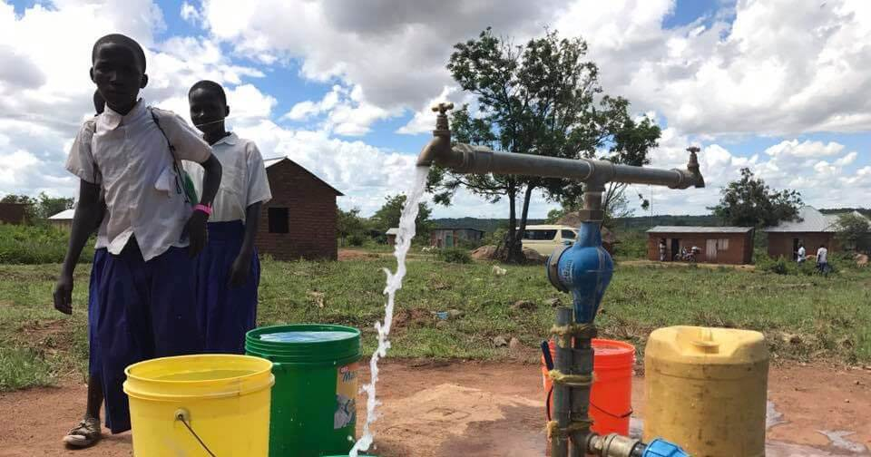 Photo of children filling up buckets with water