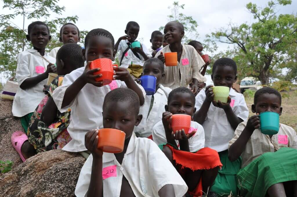 Photo of a group of children holding cups of water
