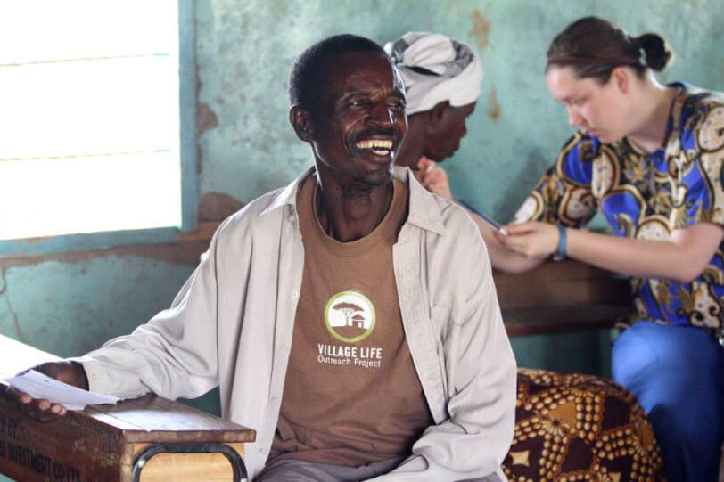 Photo of man wearing a Village Life Outreach Project t-shirt, smiling