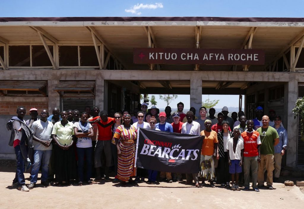 """Large group of people standing in front of Kituo Cha Afya Roche holding a """"Cincinnati Bearcats"""" flag"""